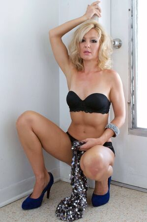 squatting: A beautiful blonde woman is squatting in front of a door in her underwear and holding her dress in her hand.