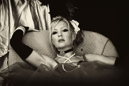 moll: Sepia toned image of old time madam or saloon girl sitting back on sofa looking at viewer seductively. Stock Photo
