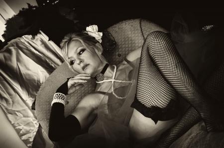Sepia getönten Bild der alten Zeit Madam oder Saloon Girl sitting on Sofa suchen, wie Sie jemand wartet  Standard-Bild