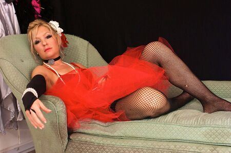 fishnets: beautiful blonde woman dressed up as old fashioned madam or prostitute, could also be a sexy elf or mrs. claus for christmas, looking directly at viewer.  Shot with blue and red strobes. Stock Photo