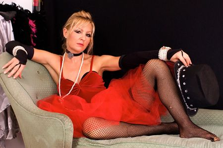 Beautiful blonde womanin costume as madam or prostitute, could also be a sexy elf or mrs. claus for christmas, looking directly at viewer.  Shot with blue and red strobes.