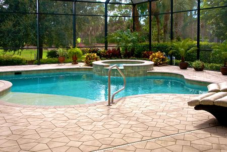 Large swimming pool surrounded by plants and screened in lanai. Stock Photo
