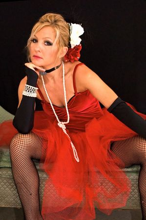 legs spread: Hermosa rubia sentado con las piernas separadas se viste como tiempo viejo bailando la ni�a o prostituta tambi�n puede ser un elfo sexy de la Sra. claus o de santa para Navidad. Mejorado con estroboscopios colores azules y rojos, para a�adir color �nico. Foto de archivo