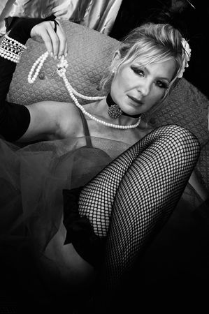 black and white image of woman dressed up in fancy old fashioned clothes and fishnet stockings.