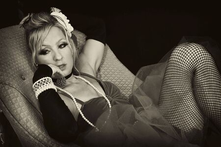 knees bent: beautiful blonde woman laying on sofa looking to side with finger in her mouth finished in sepia. Stock Photo