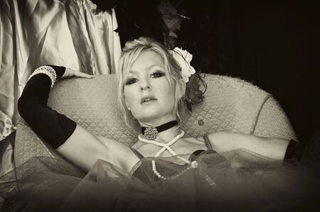 beautiful blonde woman laying back is sexy outfit looking at viewer with mouth slightly open in sepia photo