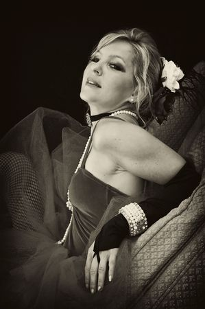 A pretty blonde woman is laying back on her elbows with head tilted back looking at viewer in sexy outfit in sepia photo