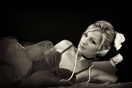 woman in old fashioned sexy outfit laying down looking at viewer, finished in sepia. photo