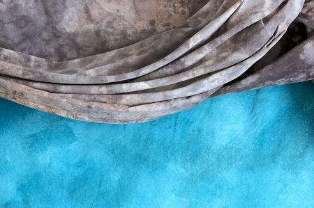a grey mottled backdrop is draped over a blue mottled backdrop cloth. Imagens