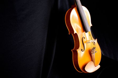 backdrop: a beautiful violin is leaning against a black backdrop at slight angle with copy space