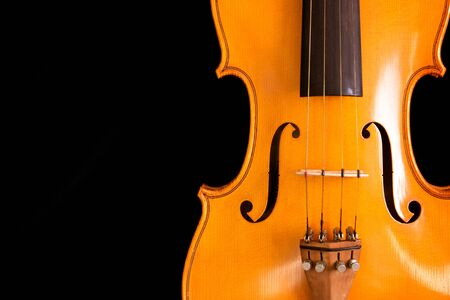 close up of waist of violin on black background