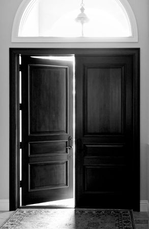 Black and white image of large dark wooden enrty doors with arched window above Stock Photo