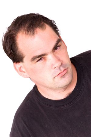 a serious looking man with receding hair line is looking directly at viewer against white photo