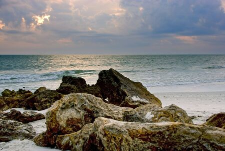 craggy: craggy rocks and boulders on the beach lead the viewers eye into this beautiful sunset image of  floridas naples beach in the gulf of mexico