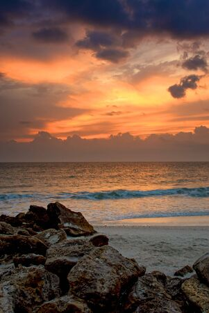 craggy rocks and boulders on the beach lead the viewers eye into this beautiful sunset image of florida's naples beach in the gulf of mexico