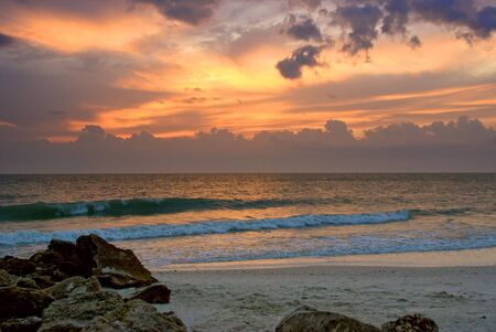 craggy rocks and boulders on the beach lead the viewers eye into this beautiful sunset image of  floridas naples beach in the gulf of mexico photo