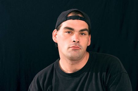 felon: a handsome tough guy wearing black against a black background is staring directly at viewer, he looks like he could be a felon or criminal Stock Photo