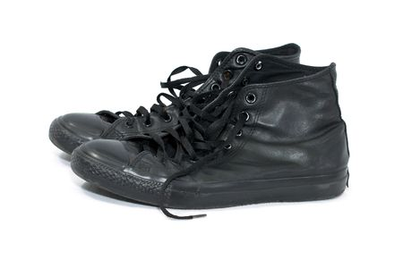 two old worn black leather high top basketball shoes on white photo