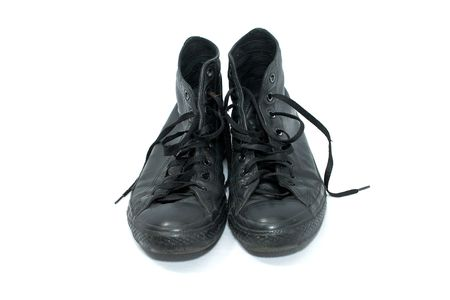 pair of old worn black leather high top basketball shoes on white, front view photo