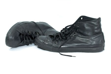 old worn black leather high top basketball shoes on white, one is laying on its side photo