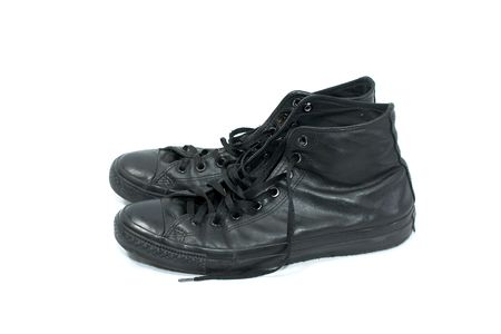 pair of old worn black leather high top basketball sneakers on white from side photo