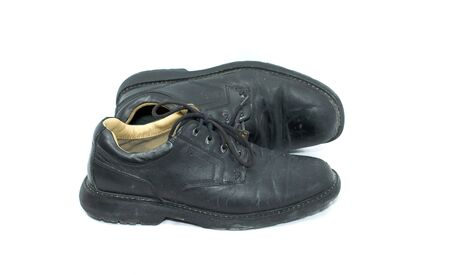 pair of black leather shoes with thick soles, on white