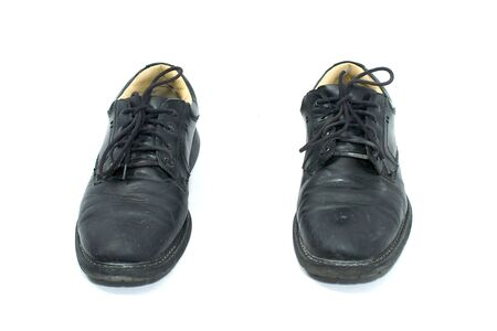 pair of dirty black work shoes on white, seen from front