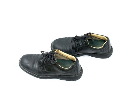 looking down on a pair of used black lace up shoes on white