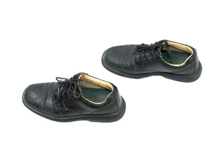 a pair of black leather walking shoes on white positioned as if walking