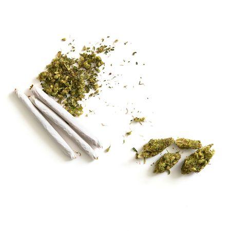 marihuana: pila de marihuana y tres articulaciones con cogollos fuera al lado sobre blanco