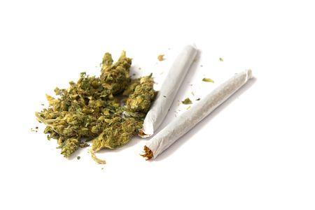 marihuana: dos articulaciones y un alijo de marihuana sobre fondo blanco