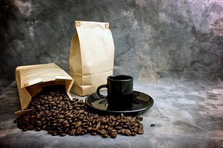 コーヒーが受け皿のまだらにされたスタジオの背景に黒のエスプレッソ カップ、閉じた袋のコーヒー全体の豆の袋を示すの美術のイメージ。空袋の