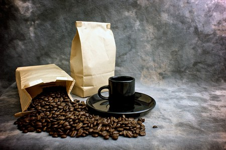 Fine art image of coffee showing a bag of whole beans, a closed bag of coffee and a black espresso cup on a saucer against a mottled studio background.  Logo or text can be placed on blank bag. Stock Photo