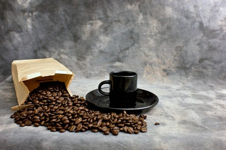 Fine art image of coffee showing a bag of whole coffee beans and a black espresso cup on a saucer against a mottled studio background.