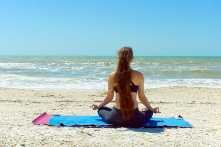 A woman with long hair is facing away from viewer looking at the sea while mediataing outside at the beach in yoga lotus position. photo