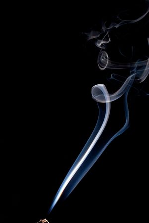a wispy cloud of real incense smoke floats up the image and starts coming back down forming abstract designs, the incense stick can be seen at the very bottom. photo
