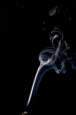 a wispy cloud of real incense smoke spirals up the image and starts coming back down forming abstract designs, the incense stick can be seen at the very bottom. photo