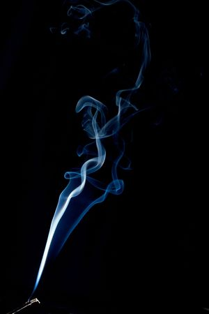 a wispy cloud of real incense smoke floats up the image forming abstract designs, the incense stick can be seen at the very bottom. photo