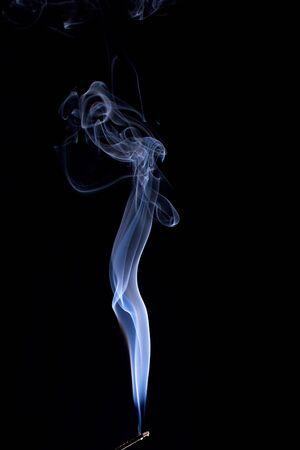 backlit image of burning incense stick against a black background Banco de Imagens