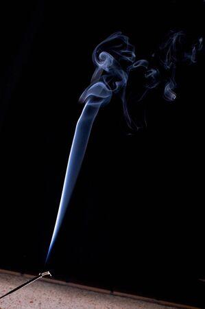 stick of incense burning against a black background Banco de Imagens