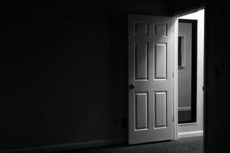 문이 열려 있고 방의 외부에서 들어오는 빛이있는 어둡고 신비한 방에서 바라본다. 스톡 콘텐츠