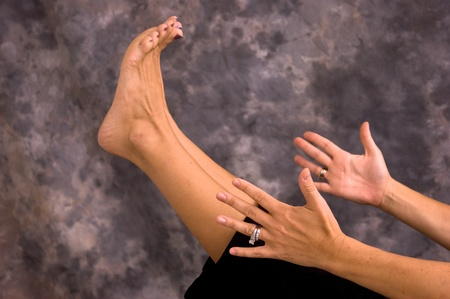 Close up of hands and feet while female yogi is in boat pose asana