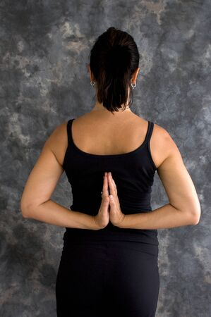 yogini: A brunette caucasian woman is standing in black yoga clothing with her hands behind her back in reverse prayer Stock Photo