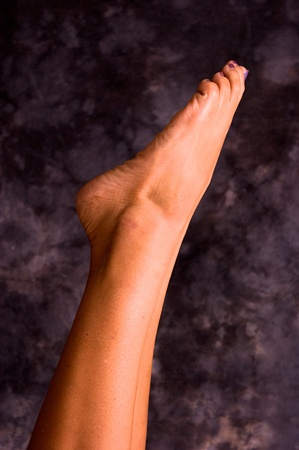 Close up of womans feet pointing up into the air while doing yoga photo