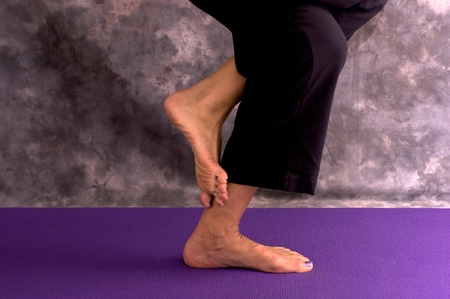 A woman practicing yoga is standing on a purple mat, images shows her feet in eagle pose