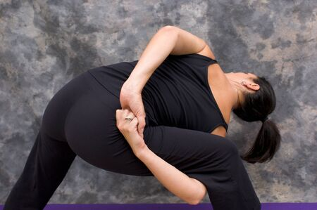A caucasian brunette woman in black clothing is seen from behind doing a yogic side angle bind pose against a mottled background