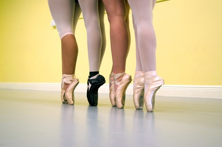 Four ballerinas are standing on their toes, on pointe, wearing ballet shoes and tights of various types during dance class. Stock Photo