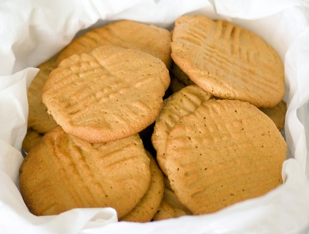 A paper towel lined container holds a batch of fresh homemade peanut butter cookies with fork marks in them, natural lighting.