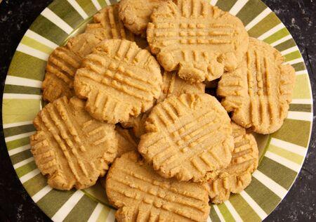 縞板はそれら、自然な照明のフォークのマーク付きの新鮮な自家製ピーナッツ バターのクッキーのバッチを保持します。