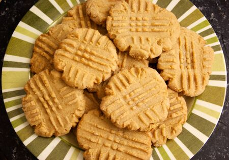 A striped plate holds a batch of fresh homemade peanut butter cookies with fork marks in them, natural lighting.
